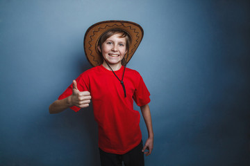 Boy, teenager, twelve years in the red t-shirt with a cowboy hat