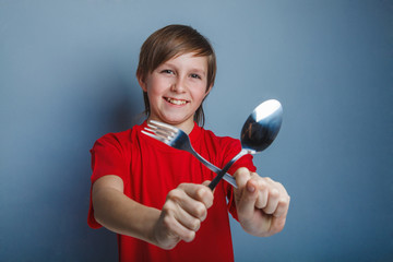 Teenager boy in red shirt twelve years holding a spoon and fork,