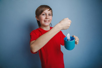 Teenager boy twelve years in a red shirt holding a cup of tea, a