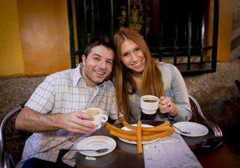 young American tourist couple having spanish typical churros