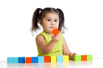 kid plays with building blocks and learning of colors