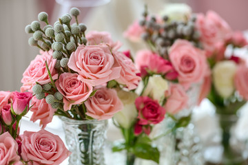 Bouquets of roses on a festive wedding table in the restaurant.
