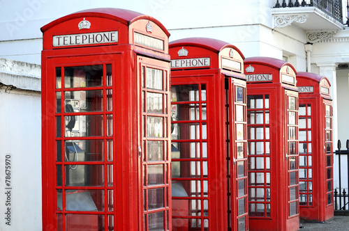 Row of red telephone boxes in London street Poster