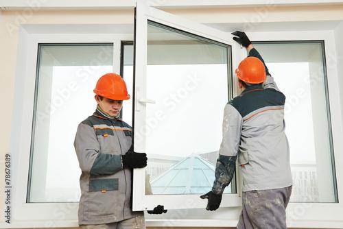 Leinwanddruck Bild two workers installing window