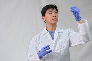 Scientist holding test tube and safety glasses