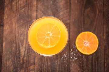 Top orange juice in glass, fresh fruits on wooden background