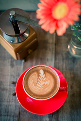 Red coffee mug , coffee grinder on wooden background.
