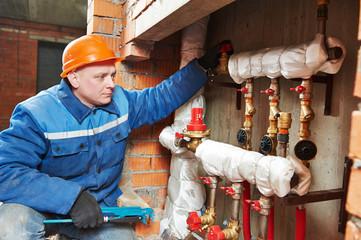 heating engineer repairman in boiler room