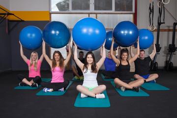 Medicine ball fitness training - sports team sitting on yoga mat