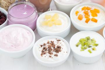 Assorted fruit yoghurts and breakfast ingredients, close-up