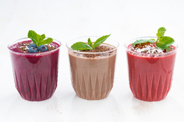 chocolate, blueberry and strawberry milkshakes in glasses