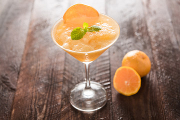 Orange juice in glass, fresh fruits on wooden background