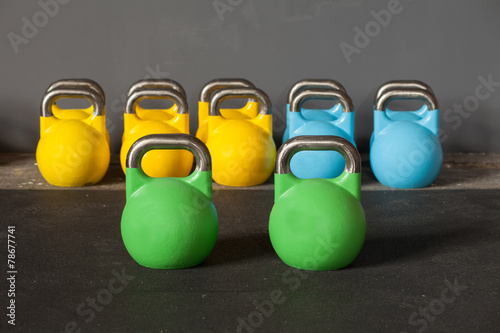 Poster colorful kettlebells in a row in a gym - focus on the front kett
