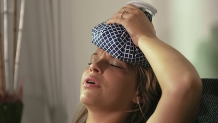 Woman With Headache Sitting On Sofa With Ice On Head