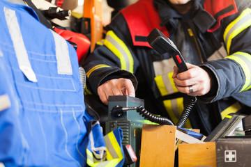 Feuerwehrmann bedient Funkgerät im Löschfahrzeug