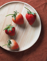 Fresh strawberry on wood plate