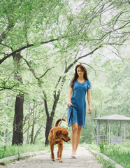 Young woman walking with a dog
