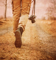 Traveler with photo camera walking on path, vintage image