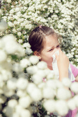 Little girl is blowing her nose, selective focus
