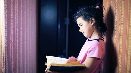 Teen girl child reading book while standing against a wall in