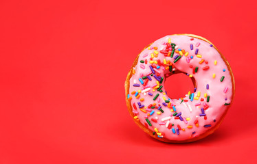 Donut with sprinkles over red background