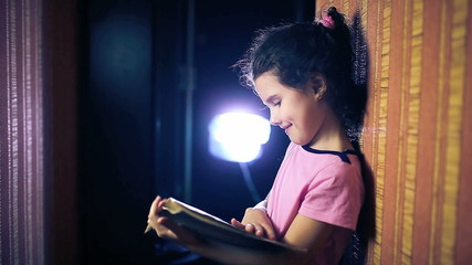 Teen girl child reading book while standing against wall in