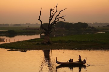 Boat on lake at sunset neat U Bein bridge Mandalay