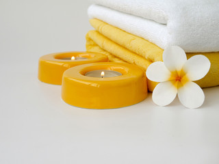 Towels, two candles and frangipani flower