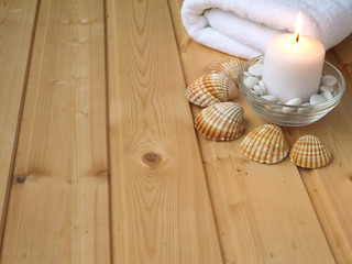 Towel,shells and burning candle on the wooden background