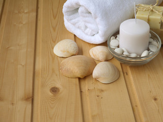 Towel,soap,candle and shells on the wooden background
