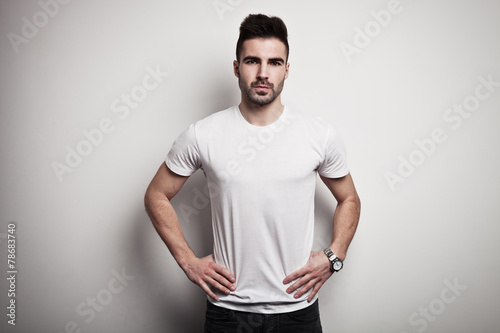 Serious young man in white blank t-shirt