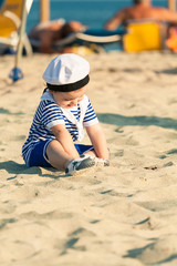 Sweet smiling toddler dressed as a sailor sitting on a beach and