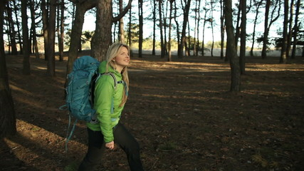 Hiker blonde woman walking hiking in forest with backpack