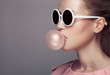 Beautiful blonde woman. Fashion portrait. Blowing bubble gum.