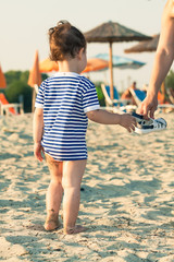 Woman hand giving flip flops to a toddler with sailor shirt on a