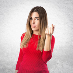 Young girl doing a money gesture over white background