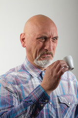 Portrait of a man drinking a coffee disgusting