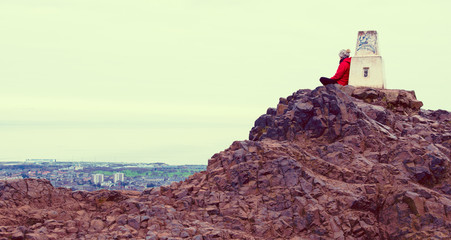 Girl enjoying view of Edinburgh from top of Arthurs seat, UK