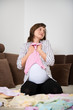 Joy - pregnant woman with baby clothes