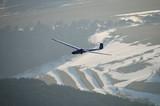 Segelflugzeug über winterlicher Landschaft