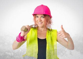 Worker woman with her thumb uo over white background