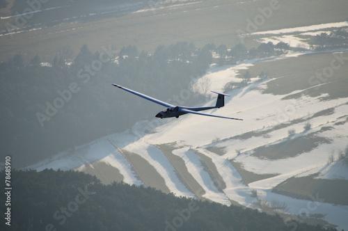 Leinwanddruck Bild Segelflugzeug über winterlicher Landschaft