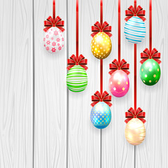 Easter eggs with bow on wooden background