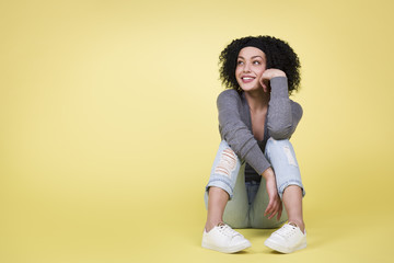 Joyful woman looking up sitting on isolated yellow  background.