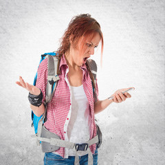 frustrated backpacker talking to mobile over white background