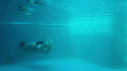 The man swims under water in the poolStock video:
