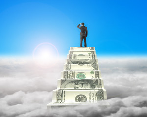 Businessman reaching the top of money stairs with sunlight cloud