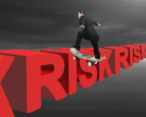 Businessman skating on money skateboard across red risk 3D text