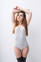 Portrait of a young sexy woman posing over gray background