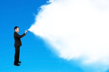 Business man spraying white cloud paint isolated on blue